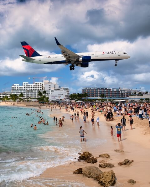 A large jet landing, viewed from the beach bar