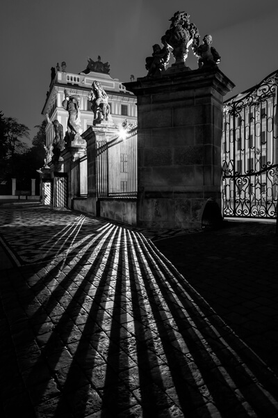 Night play of shadows in front of the Wrestling Titans statues on the Prague Castle