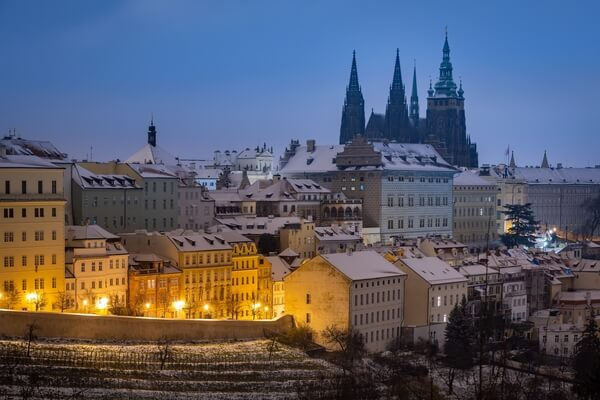 Winter view of Prague Castle with Uvoz street lit by lamps.