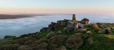 The view of the trig point looking north to Cosdon Hill on a spring sunrise during a temperature inversion.