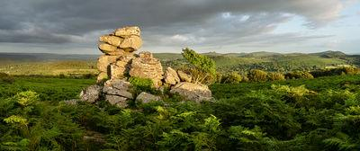 The view of the rock outcrop looking south to Haytor and Hound Tor on a summer sunset.
