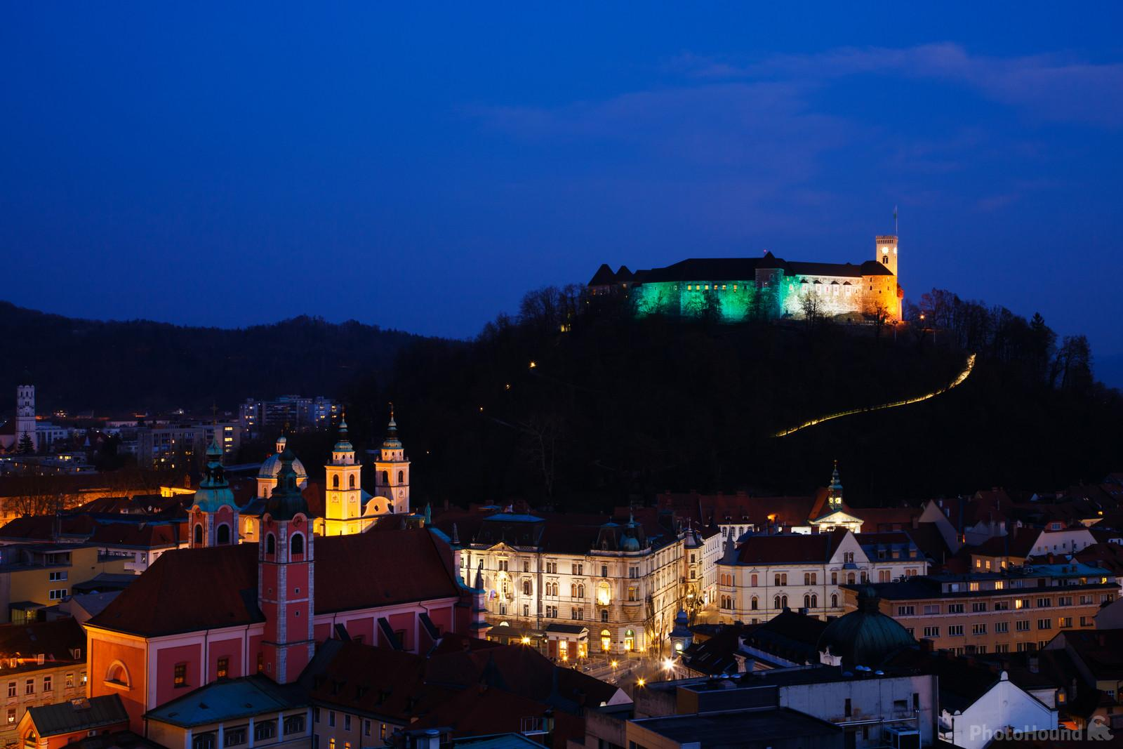 View from Neboticnik at dusk of the Ljubljana Castle lit up in the colours of the Irish flag for Saint Patrick's Day.