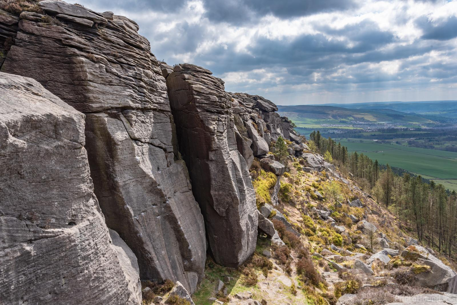 A beautiful gritstone climbing crag, high over the valley with Skipton in the distance.