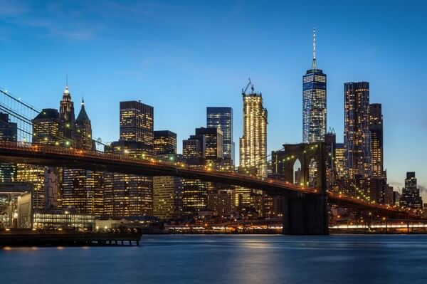 Evening shot of the Brooklyn Bridge with illuminated panorama of Lower Manhattan in the background.