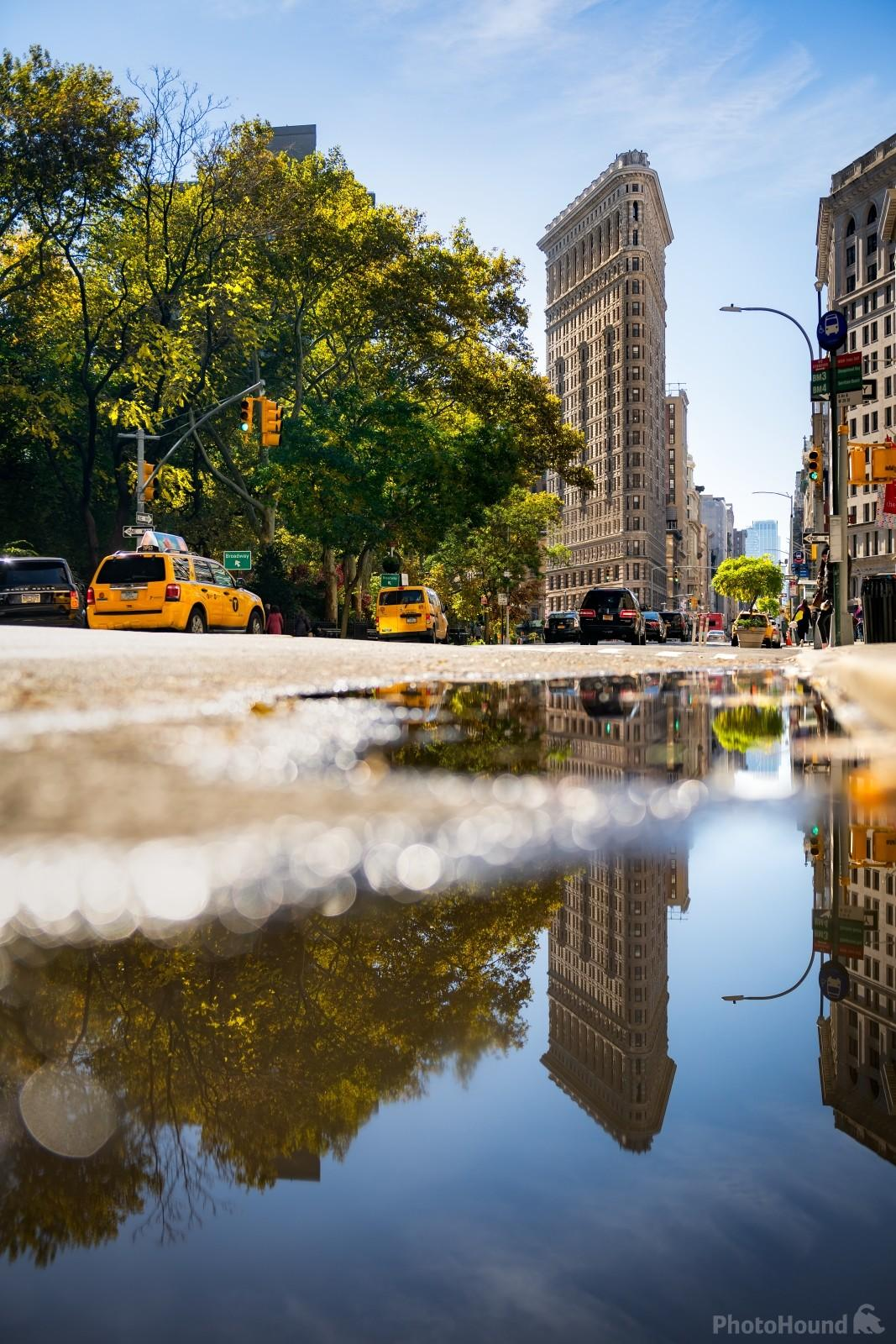 Flatiron Building reflecting in the water puddle