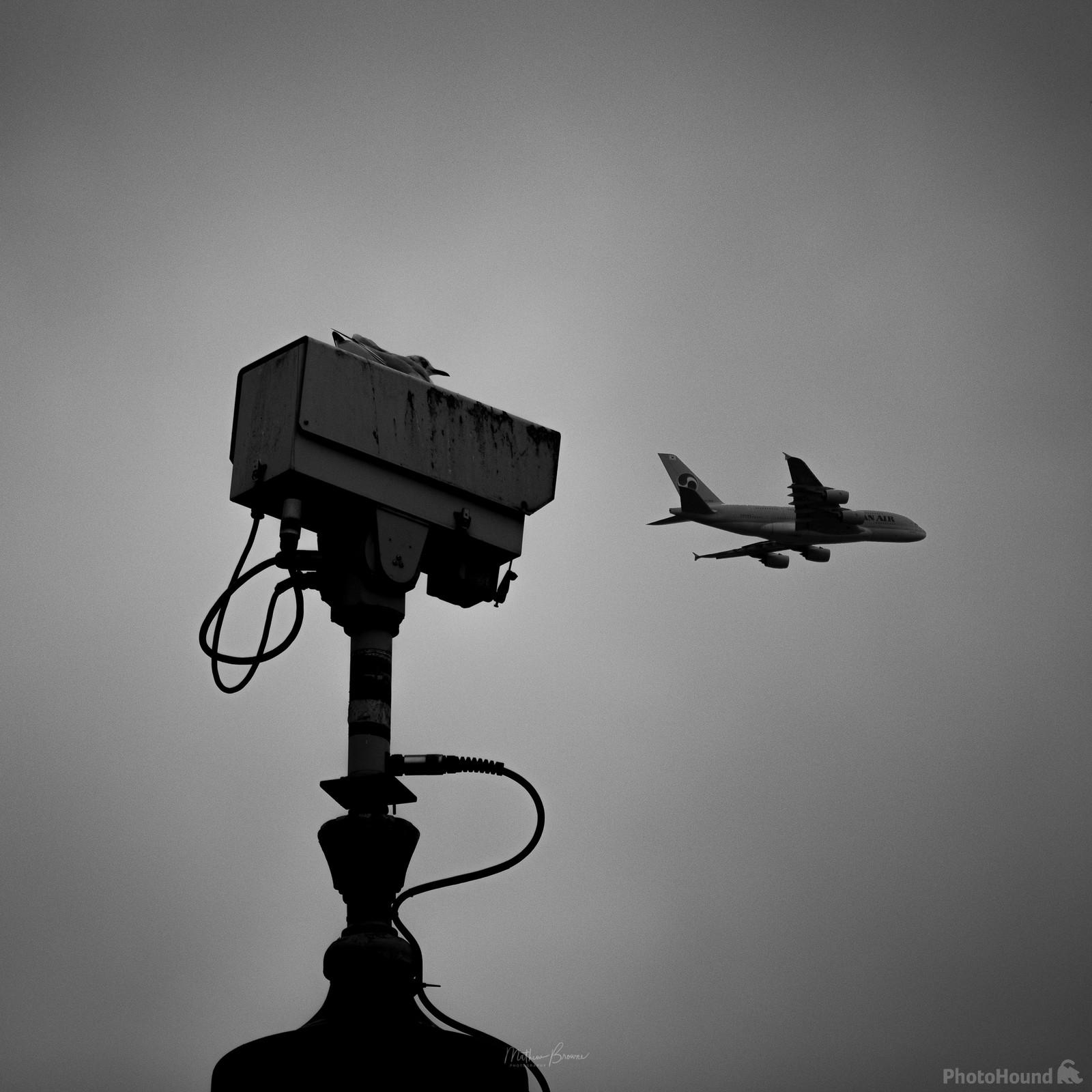 A telephoto lens of the Square's CCTV cameras and a passing plane