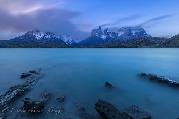 I just returned from Patagonia. We had planned to stay at the Hosteria Pehoe, but found that it had failed an inspection and was closed.  We had to find another place to stay and drive to get there, but the scenery is spectacular.  This was a very windy and cold evening blue hour on the island.