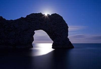 Durdle Door photographed in June as the moon rose over the arch.