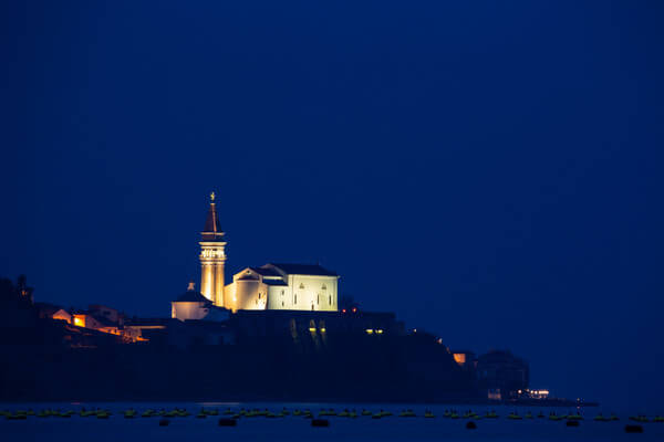 View of Saint George's Parish Church in Piran at dusk, seen from Strunjan, on the Adriatic Coast in Slovenia.