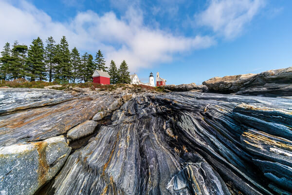 A low view with a wide angle lets you lead up to the lighthouse with the lines in the rocks