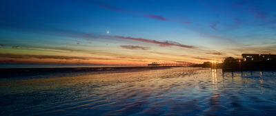 Taken one evening at sunset, looking east, the moon was perfectly positioned as a crescent above the pier