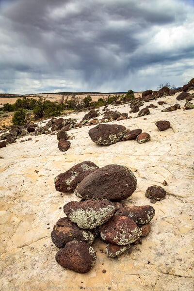 Volcanic boulders on white sandstone along trail