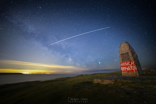 "Taken near the Salt House, at the Port Eynon view point.  The graffiti was painted by an unknown person sin solidarity with the Welsh ""Cofiwch Dryweryn"" movement (though this homage has a spelling error).  Flying over head were the first passing of the Space X Starlink satellites."