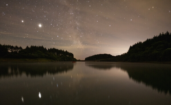 night image looking across the reservoir with jupiter and saturn and the milky way