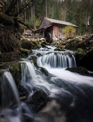 A wooden mill below the waterfall.