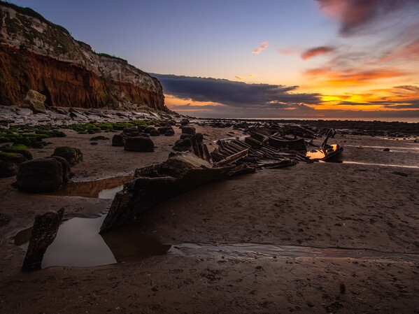 Old Sheraton steam ship wreck and Hunstanton Cliffs during the sunset.