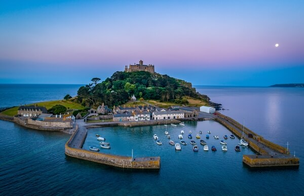 Mid level drone shot of St Michaels Mount Cornwall with the full moon behind