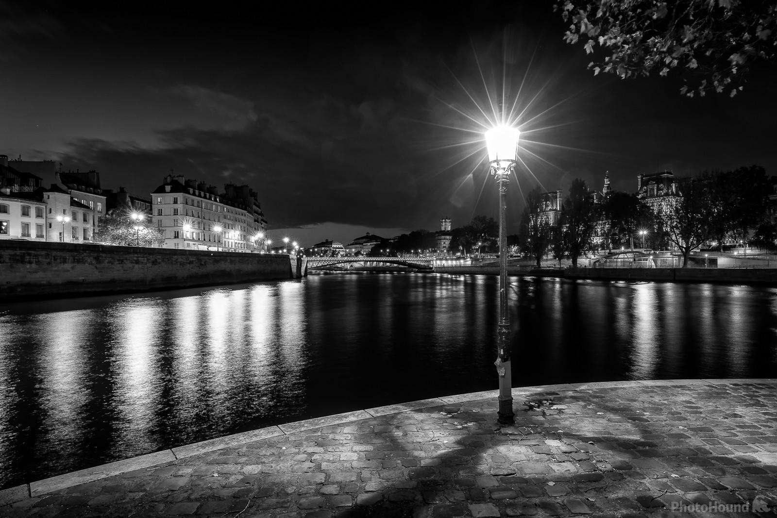 Start of night on the Square Louis Aragon at the end of Ile St-Louis in Paris in B/W. In the distance, you can see Pont d'Arcole on the Seine, the Paris City Hall, the city Theater, the Chatelet Theater and the Tour Saint-Jacques.