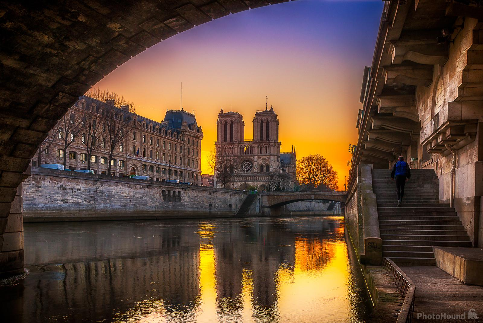 Sunrise behind the Cathedral Notre Dame de Paris and the police headquarters seen from under the Pont St-Michel, Promenade René Capitan along the Seine. We also see the Petit Pont.